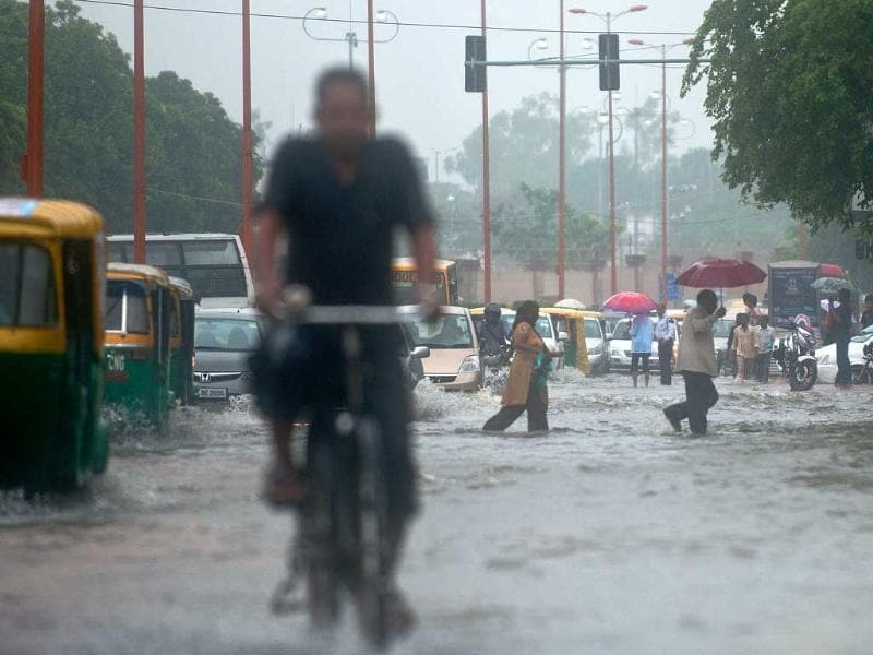 Office-goers wade through a water-clogged road following heavy rainfall in New Delhi.