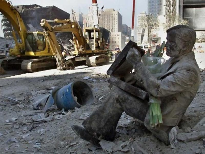 A dust covered bronze statue of a man with his briefcase rests in the rubble of the World Trade Center on 13 September 2001, in New York. The statue once rested on a bench near the towers and now holds flowers and a note reading