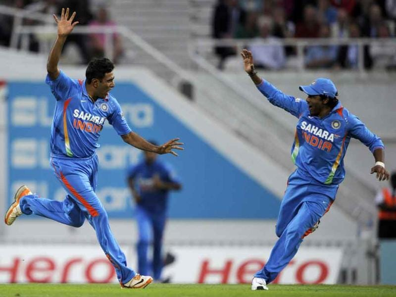 Ravichandran Ashwin celebrates with Ravindra Jadeja after he claims the wicket of England's Jonathan Trott during their one day international cricket match at the Oval cricket ground, London.