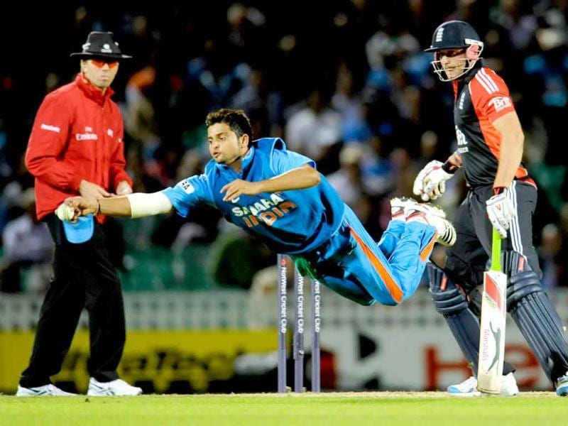 Suresh Raina dives to stop a ball watched by England's Tim Bresnan and umpire Nigel Llong during the third one-day international cricket match at the Oval cricket ground in London.