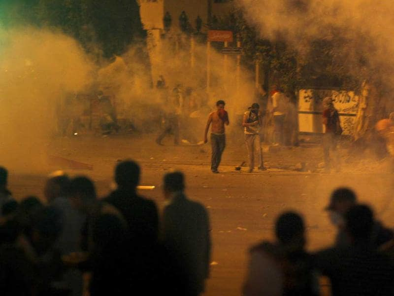 Protesters throw stones as tear gas is seen around them during clashes with Egyptian security forces next to a building housing the Israeli embassy in Cairo, Egypt.