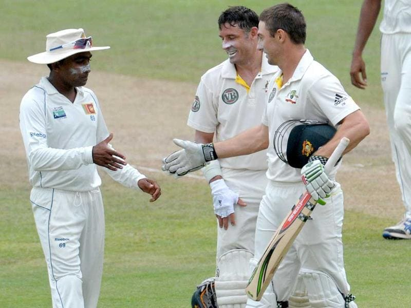 Sri Lankan cricketer Mahela Jayawardene (L) congratulates Australian cricketer Shaun Marsh (R) after he scored a century as Michael Hussey (C) looks on during the third day of their second Test cricket match in Pallekele.