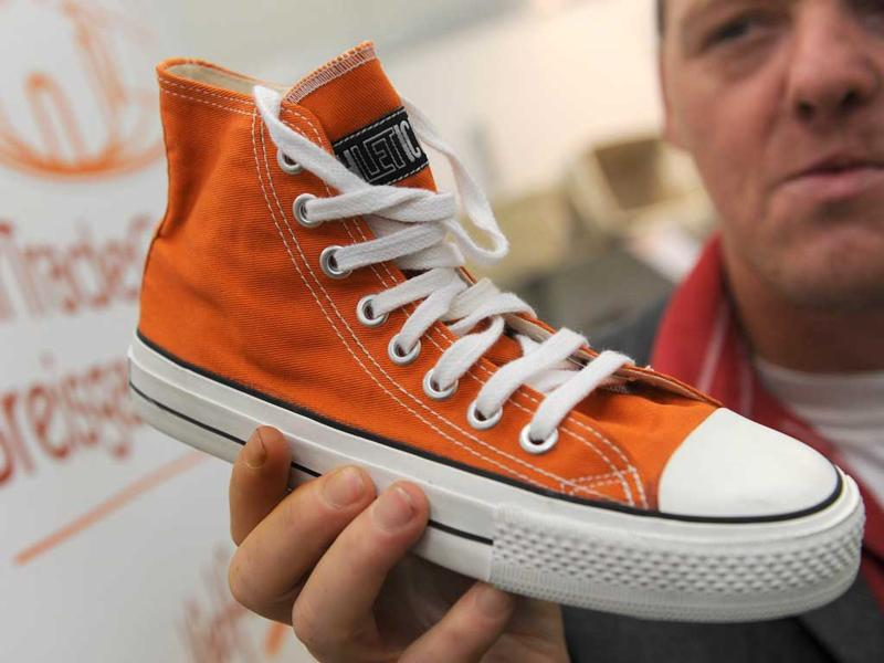 German distributor Thilo Rau holds a fair trade sneaker shoes made with rubber from India and cotton from Sri Lanka, in Dortmund, western Germany, during the