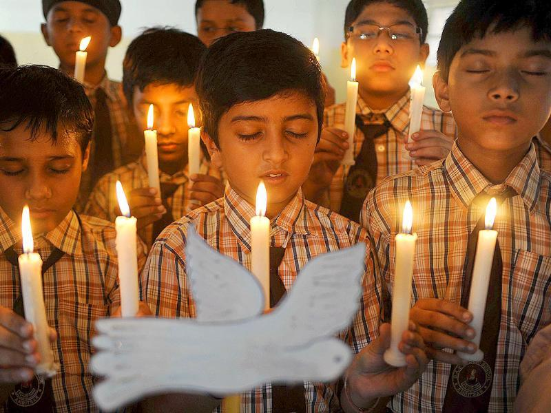 School children hold candles as they pay tribute to those killed in the September 11, 2001 attacks on New York's World Trade Centre twin towers, at a public school in Amritsar.