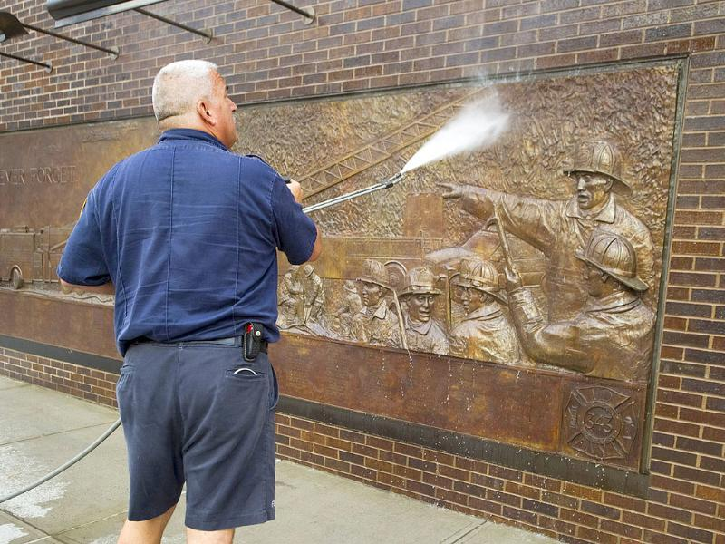 A fireman washes a memorial for firefighters on the wall of a station near the World Trade Center in New York.