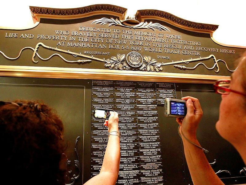 People photograph names of loved ones on a plaque in honor of FDNY firefighters who have died from illness related to working at Ground Zero in New York City.
