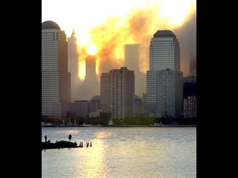 Smoke from the destroyed World Trade Center rises over the southern end of New York City's Manhattan Island nearly blocking the sunrise as seen from Jersey City, New Jersey in the early morning, 12 September, 2001. Terrorists hijacked two commercial airliners and crashed them into each of the towers of the Trade Center. File photo
