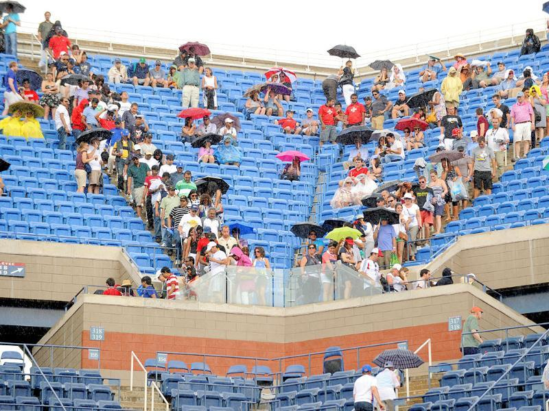 Fans leave their seats at Arthur Ashe Stadium court as rainfall delays the Men's semifinal match between number one seed Novak Djokovic of Serbia and number three seed Roger Federer of Switzerland at the US Open tennis tournament.