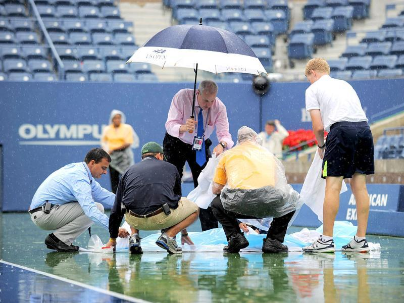 Workers cover a painted sign commemorating the 10th anniversary of 9/11 terror attacks on the court as rainfall delays the Men's semifinal match between Novak Djokovic of Serbia and Roger Federer of Switzerland at the US Open tennis tournament.