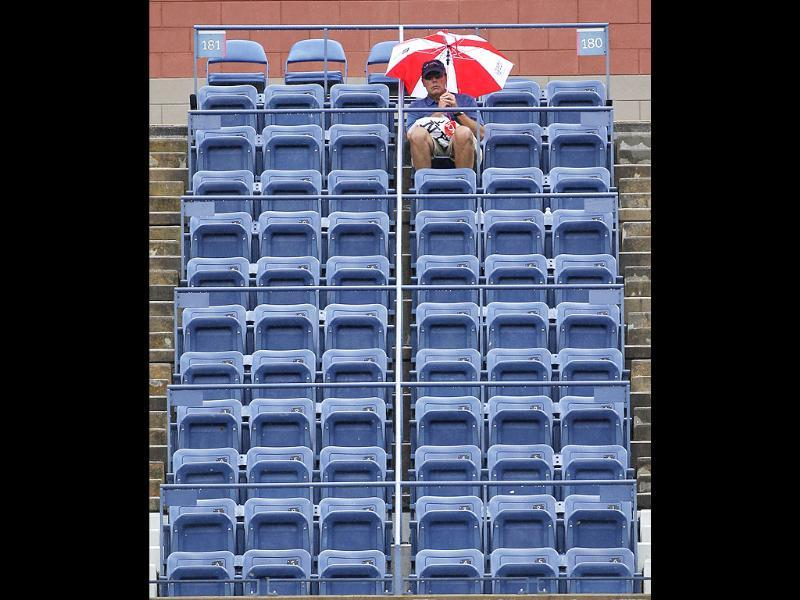 A patron waits in the rain for the start of a semifinal match at the US Open tennis tournament in New York.