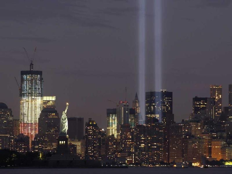 The Tribute in Lights is illuminated next to One World Trade Center (L) and the Statue of Liberty (C) during events marking the 10th anniversary of the 9/11 attacks on the World Trade Center in New York.