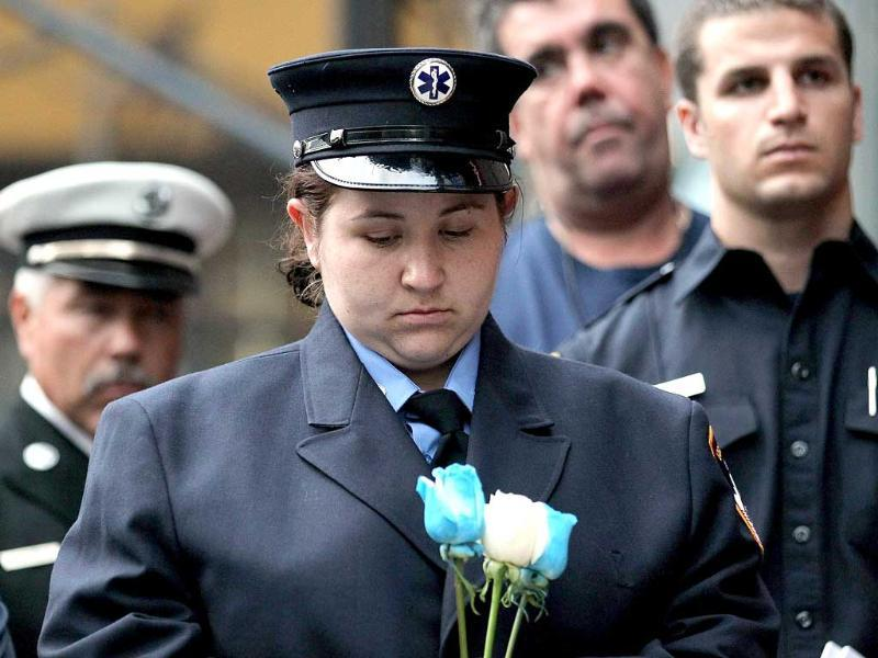 A member of the New York Fire Department EMS services holds roses during a ceremony honoring six firefighters from Engine 235, known as the Monroe 6, who died in the September 11 terror attacks.