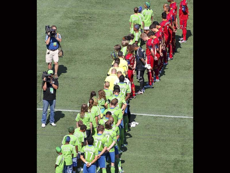 Members of the Seattle Sounders FC and Real Salt Lake observe a moment of silence in remembrance of 9/11 at Century Link Field in Seattle, Washington.