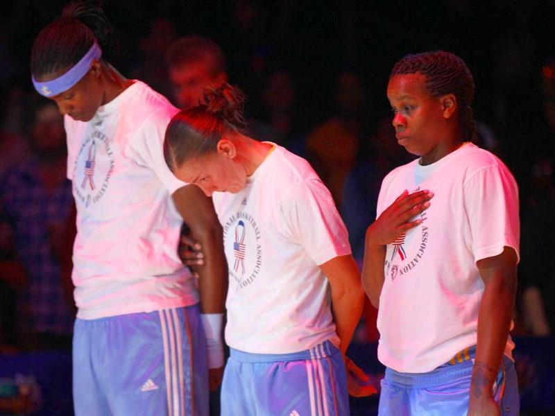 Chicago Sky's Sylvia Fowles (L) Erin Thorn and Epiphanny Prince (R) stand for a moment of silence in observance of the 10th anniversary of the 9/11 attacks before a WNBA basketball game against the Los Angeles Sparks in Los Angeles.