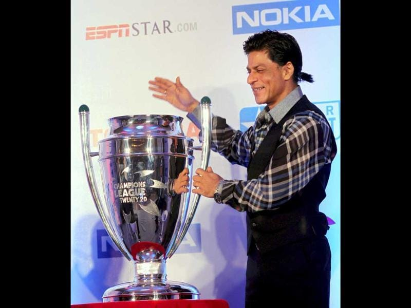 SRK playfully pats the newly unveiled Champions league T20 trophy. (PTI)