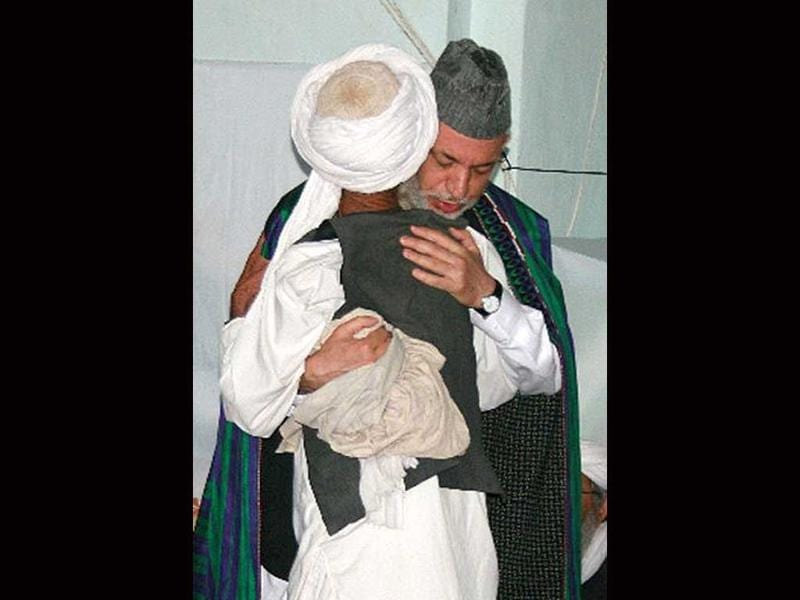 Afghanistan's President Hamid Karzai (R) hugs an Afghan man from Bala Buluk where US air strikes allegedly killed 140 civilians at a mosque in Farah city on May 19, 2009. File photo