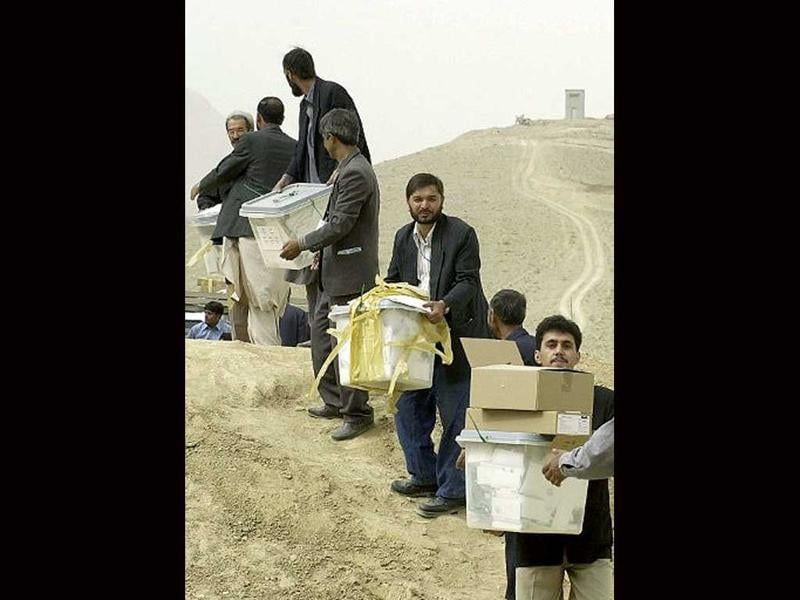 Afghan election workers stand in a queue to pass on the ballot boxes to be carried for vote counting in Kabul, 10 October 2004, at the end of the country's first democratic elections. File photo