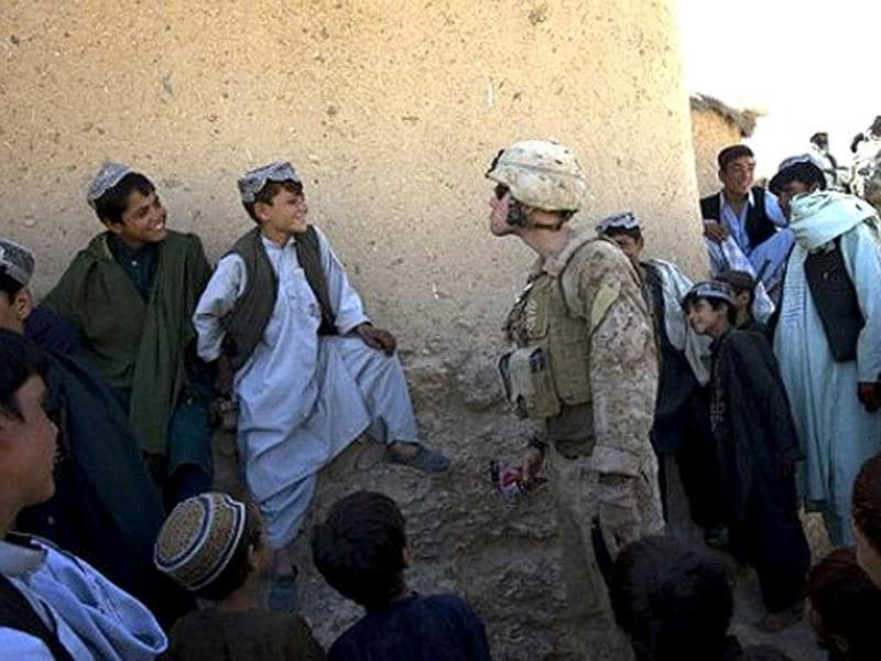 A US Marine from 2/3 Fox company jokes around with Afghan villagers staring at him while on patrol in Farah Province, southern Afghanistan, on September 23, 2009.