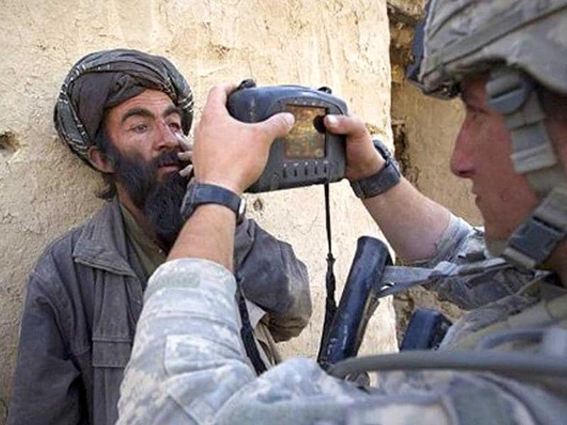 A US soldier from Bravo Troop 1-75 Cavalry 2nd Brigade 101st Airborne Division takes a picture of Afghan villager Mohammad Ras in Loya Derah village during a clearance patrol in Zari district of Kandahar province on December 28, 2010.