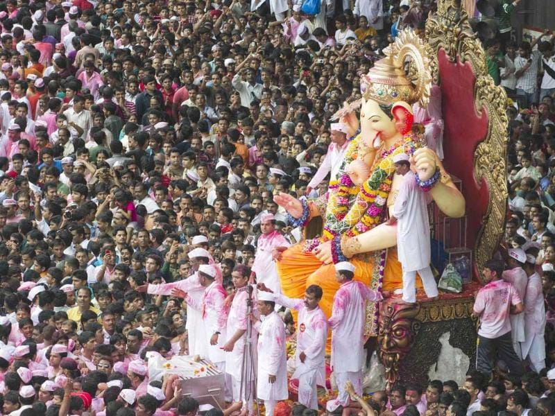 Devotees gather around a huge idol of Lord Ganesha during its procession for immersion into the Arabian Sea, on the streets of Mumbai.