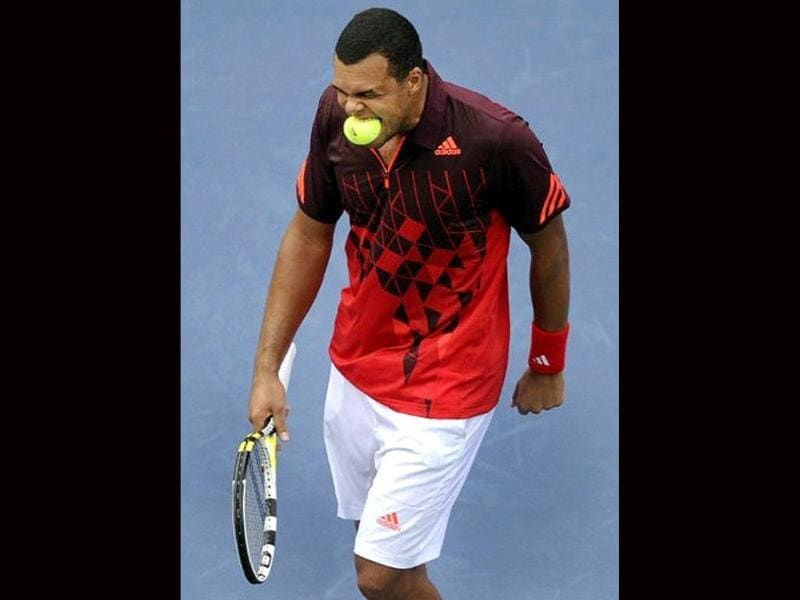 Jo-Wilfried Tsonga from France puts a ball in his mouth after a missed point against Mardy Fish of the United States during their men's 2011 US Open match at the USTA Billie Jean King National Tennis Center in New York.