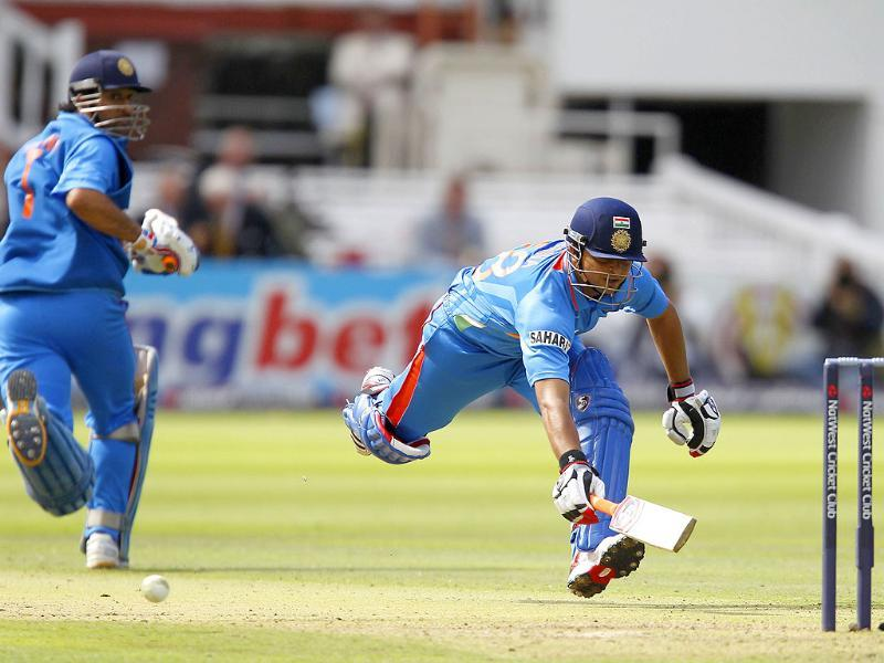 India's Suresh Raina (R) dives to avoid being run out and is successful watched by Captain Mahendra Singh Dhoni (L) during the fourth One Day International (ODI )cricket match between England and India at Lord's cricket ground in London.