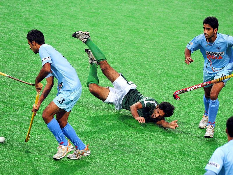 Sing Gurbaj (L) and Sharma Vikas (R) watch as Pakistan's Ahmed Fareed (C) crashes to the ground during their final match at the first Asian Men's Hockey Championship in Ordos.