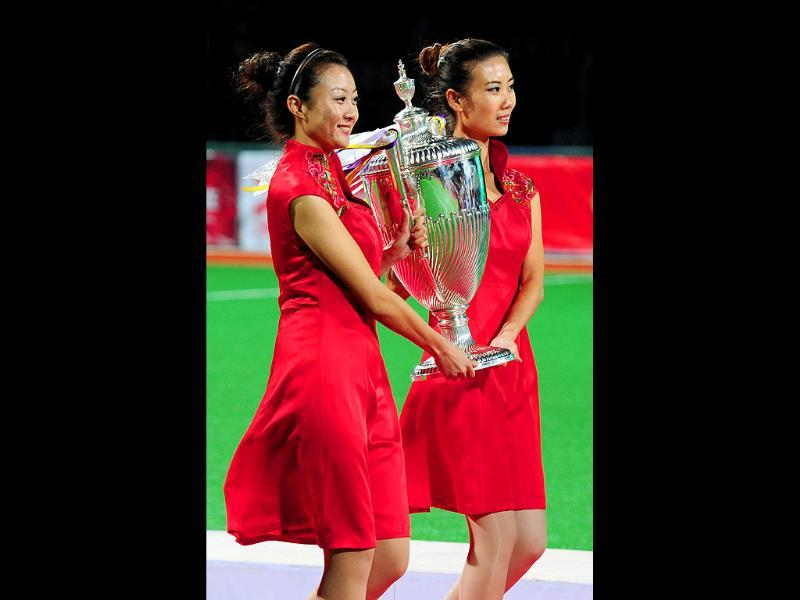 Chinese models carry the winners trophy to Indian players after they defeated Pakistan, during their finals match at the first Asian Men's Hockey Championship in Ordos.