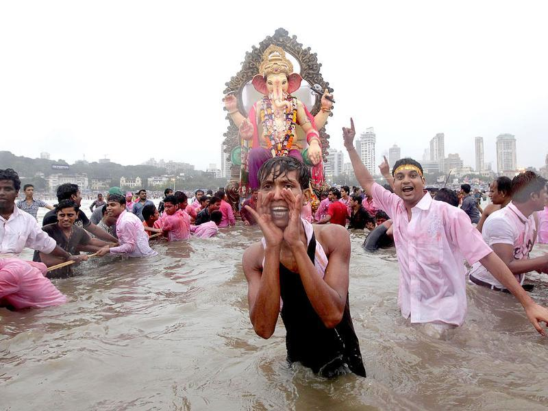Hindu devotees immerse the idols of Lord Ganesh in the Arabian Sea in Mumbai.