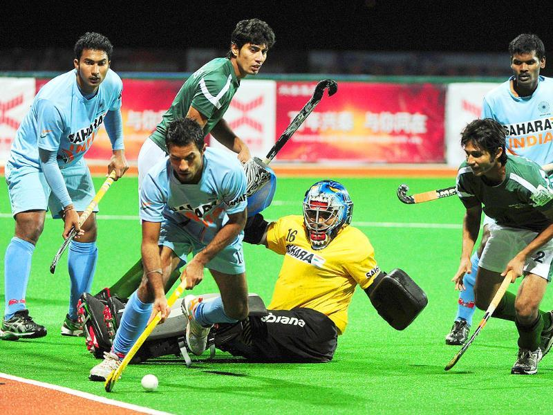 India's goalkeeper Sreejesh Parrattu Raveendran watches from the ground as teammate Gurbaj Singh (2L) clears the ball from Pakistan, during their finals match at the first Asian Men's Hockey Championship in Ordos