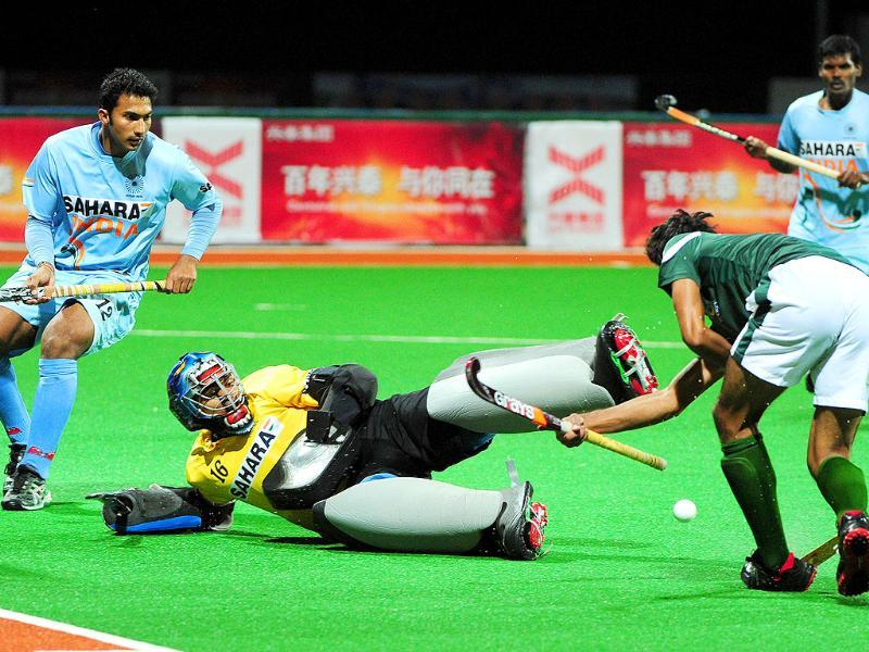 Goalkeeper Sreejesh Parrattu Raveendran blocks a shot from Pakistan's Muhammad Waqas (R), during their finals match at the first Asian Men's Hockey Championship in Ordos.