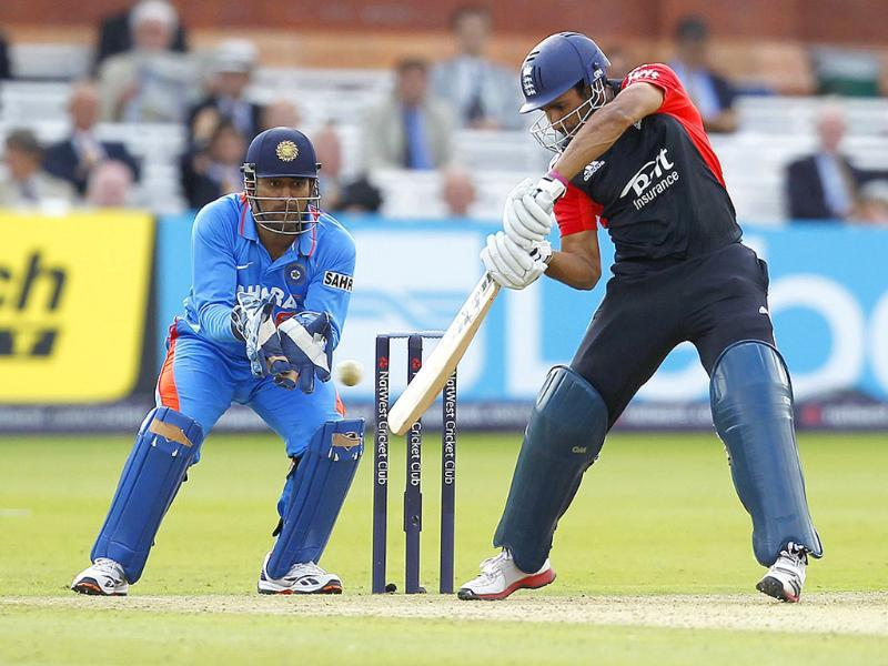 England's Ravi Bopara (R) plays a shot watched by India's Captain and Wicketkeeper Mahendra Singh Dhoni during the fourth One Day International (ODI) cricket match between England and India at Lord's cricket ground in London.