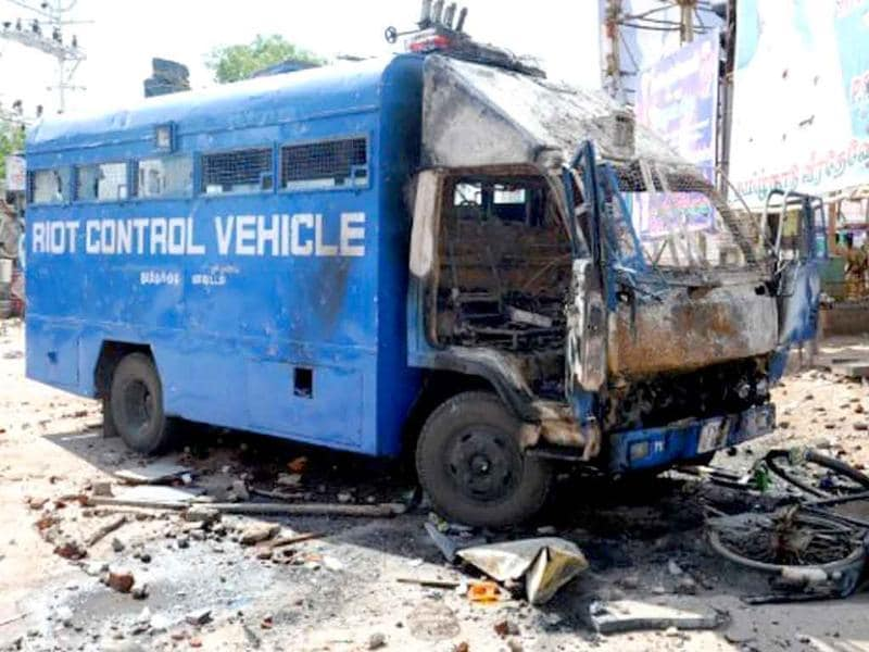 A police van sits destroyed near a store front after it was attacked by an angry mob in Paramakudi, 40 km from Ramanathapuram.