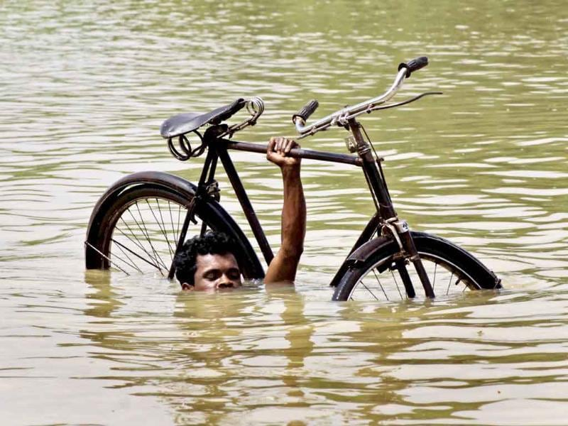 A villager wades through flooded water carrying his bicycle near Megha village, 55 kilometers from Bhubaneswar.