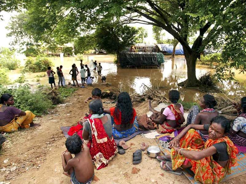 Villagers sit on dry land after their homes were flooded by the rising waters of the River Mahanadi on the outskirts of Cuttack city, about 30 kilometers from Bhubaneshwar.