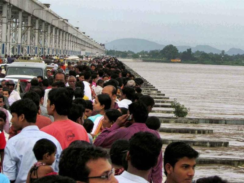 People watch the swollen Mahanadi river flowing above the danger mark near Mundali in Cuttack.