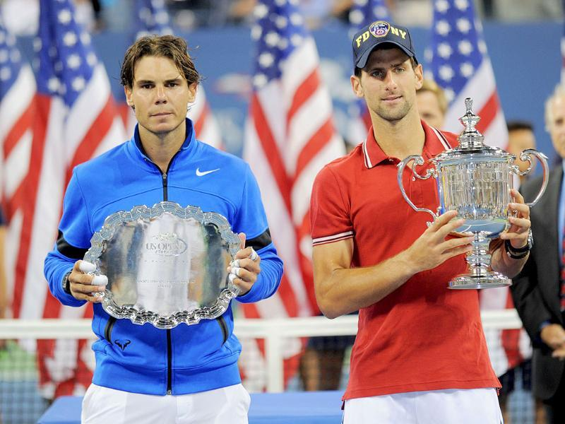 Novak Djokovic (R) and Rafael Nadal pose for photographs with their trophies after the men's US Open final at the USTA Billie Jean King National Tennis Center in New York.