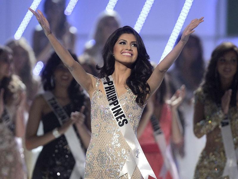 Miss Philippines Shamcey Supsup throws her arms in gay abandon during the Miss Universe pageant in Sao Paulo.