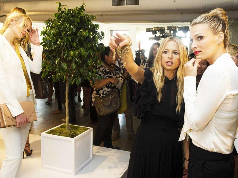 Designer Rachel Zoe (L) shows Molly Sims her Spring 2012 fashion line during Mercedes-Benz Fashion Week in New York.