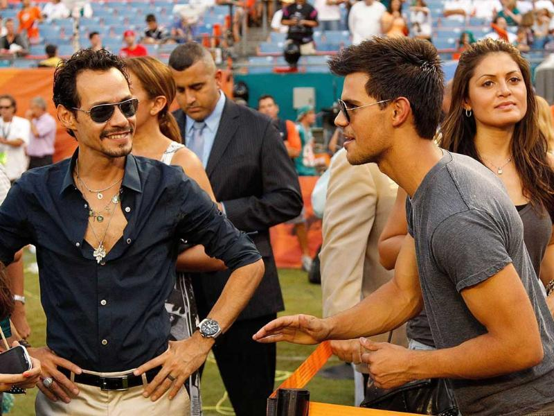 Marc Anthony greets Taylor Lautner during a game between the Miami Dolphins and the New England Patriots at Sun Life Stadium in Miami Gardens, Florida.