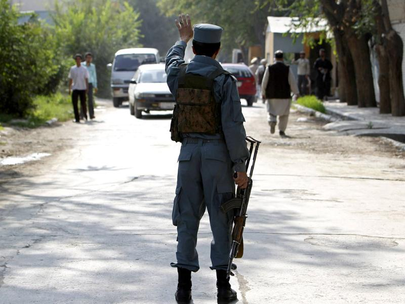 An Afghan policeman keeps watch near the site of rocket-propelled attack in Kabul.