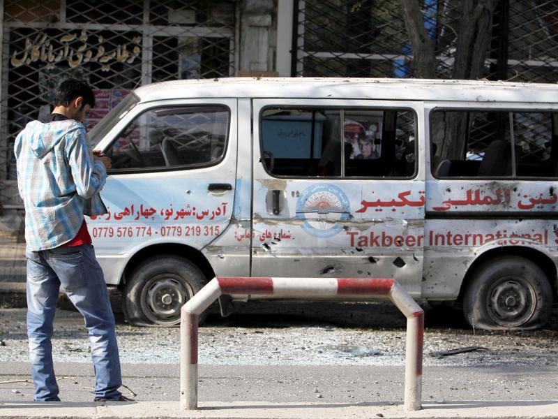An Afghan man films a car that was damaged by a rocket-propelled attack in Kabul.