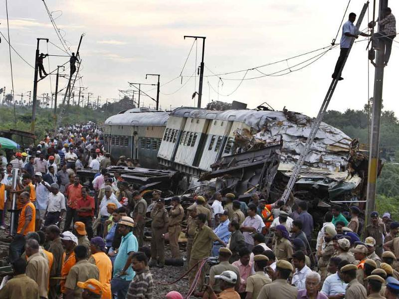 Rescue workers and others crowd next to the derailed compartments of a passenger train after two trains collided near Arakkonam, southwest of Chennai.