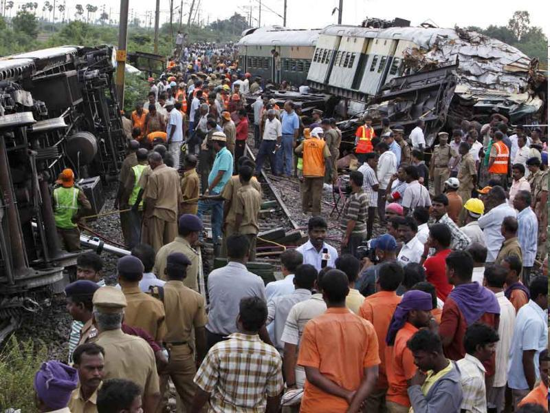 Rescue workers and others crowd next to the compartments of two trains after they collided near Arakkonam, southwest of Chennai.