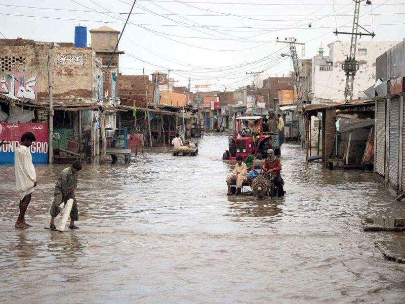 Local Pakistanis cross a flooded street in Pangrio in the flood-hit Badin district of Sindh province.