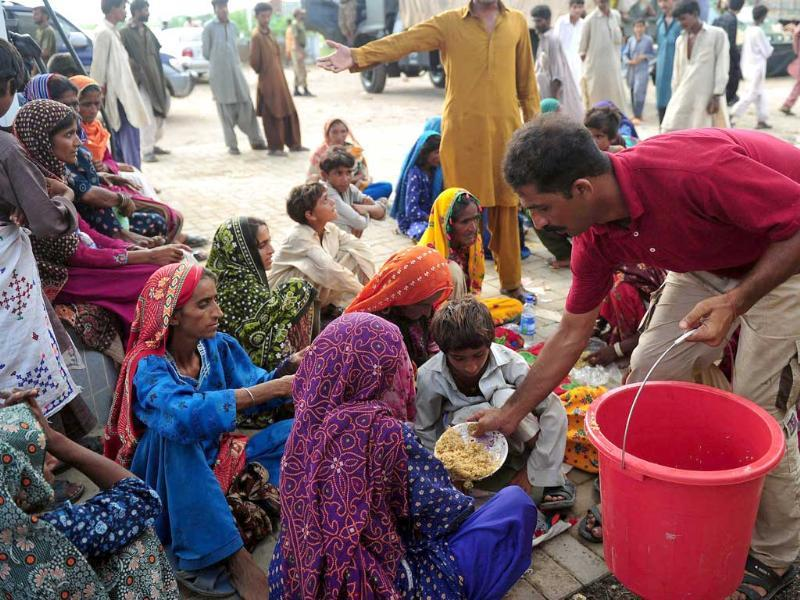 A Pakistani man distributes food to flood affected villagers at a dry area in the flood-hit Badin district of Sindh province.