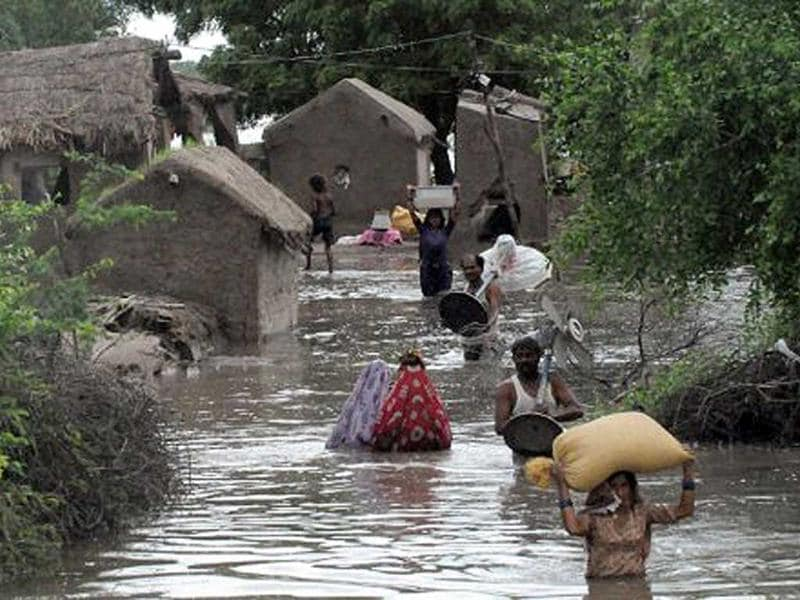 Pakistani villagers carry their belongings through flood water following heavy monsoon rain at Golarchi town in Badin district, about 200 km east of Karachi.