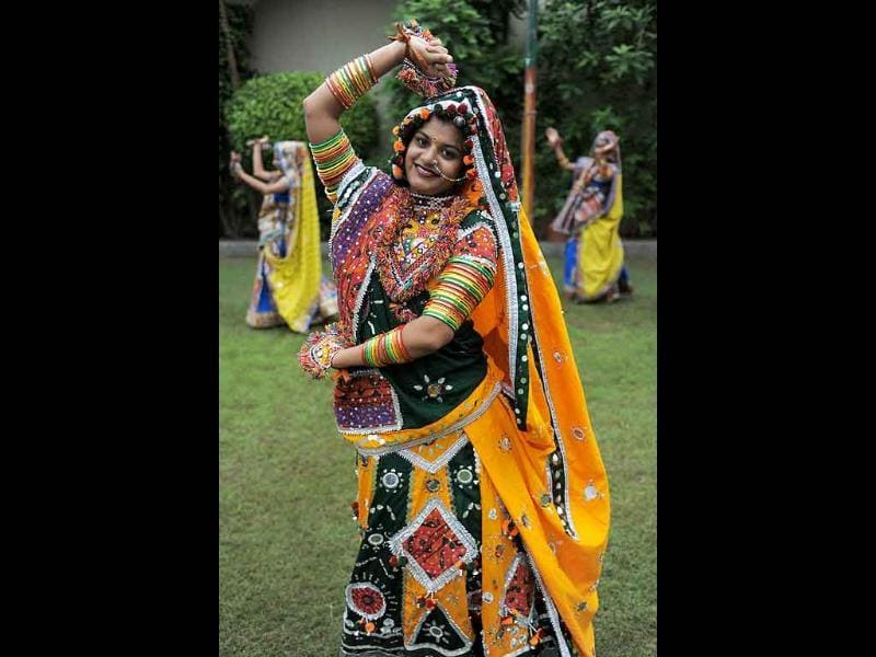 A folk dancer poses with her troupe during a full dress rehearsal for the forthcoming Navratri festival.