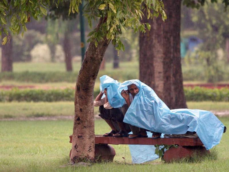 Men cover themselves with a plastic sheet to get protection from the rain at India Gate Lawns in New Delhi.