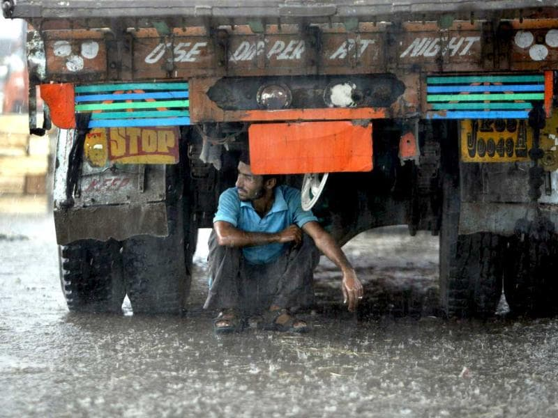 A labourer takes shelter under a truck during heavy rains in Jammu.